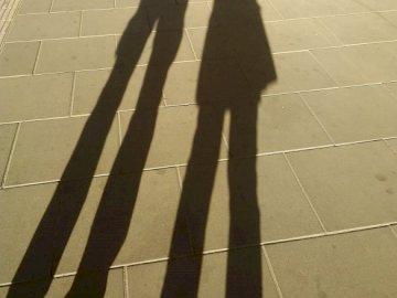 Cienie na chodniku - Cienie dwojga ludzi na chodniku w Warszawie. Osoba idąca chodnikiem.