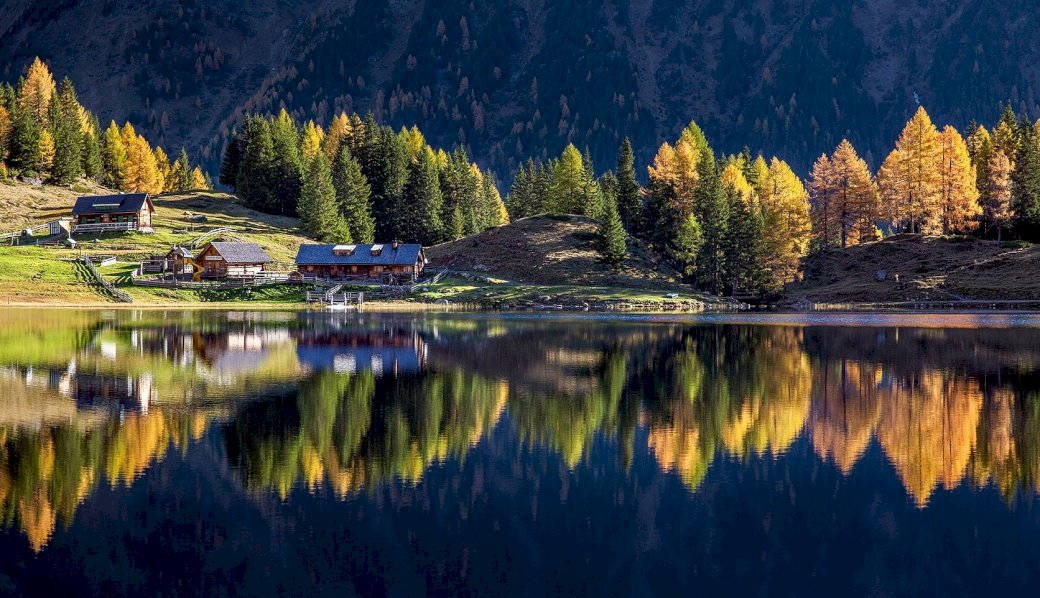 Panorama of the Alps - Austrian Alps landscape. A view of a lake surrounded by trees.