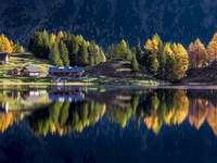 Panorama Alp - Krajina rakouských Alp. Pohled na jezero obklopené stromy.