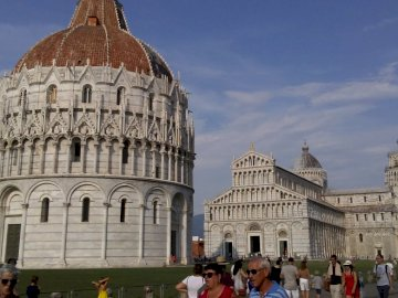 BAPTISTERIO, CATHEDRAL AND TOWER OF PISA - EMBLEMATIC RELIGIOUS SITE IN PISA. A group of people standing in front of Piazza dei Miracoli.