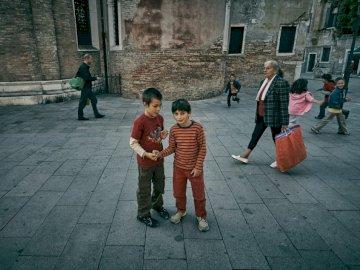 Giocare ai bambini - Due ragazzi in piedi davanti all'edificio. Drøbak, Norvegia. Un gruppo di persone che cammi
