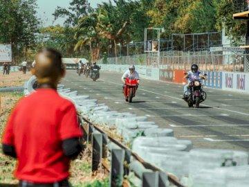 KONIEC ZDJĘĆ - Dwóch mężczyzn jedzie na motocyklach. Grupa ludzi stojących na parkingu.