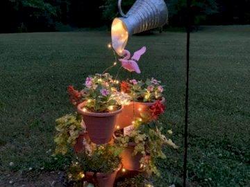 Wasserspiel - Wasserspiel mit Blumen von einem Baum. Ein Hydrant in einem Garten.