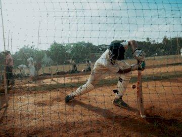 Ragazzo che gioca a cricket. - Fotografia di una partita di baseball. Un giocatore di baseball che fa oscillare una mazza a una pal