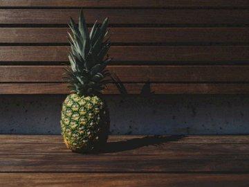 Ananas auf einer Bank - Grüne und gelbe Ananas auf braune Holzpalettenbank gelegt. Eine Ananas sitzt auf einer Bank.