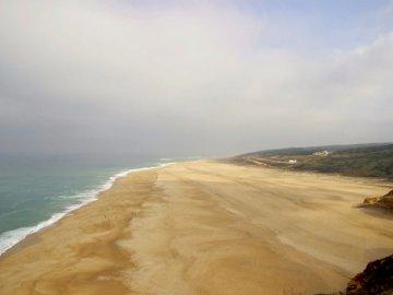Plaja Nazaré în timpul mareei joase, - Nisip maroniu. Scoţia. O plajă cu nisip lângă un corp de apă.