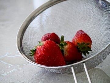 Erdbeeren in einem Sieb - Rote Erdbeeren im Edelstahlsieb. Kanada. Eine Obstschale auf einem Teller.