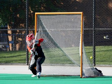 Megan Taylor - Mann im roten Helm, der Stock nahe Zielnetz hält.