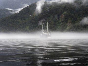 Wieczorna mgła wpada do - Łódź w ciele wody w skali szarości. Banbury, Wielka Brytania. Wodospad biegnący nad akwenem.