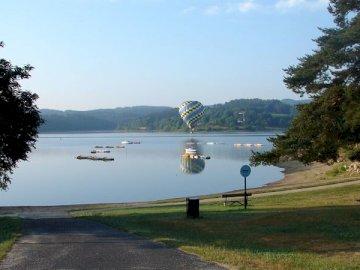 mongolfiera - mongolfiera sopra il lago. Un albero accanto a uno specchio d'acqua.