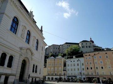 w Salzburgu - kamienice i widok na zamek -Salzburg. Zamek z zegarem z boku budynku.