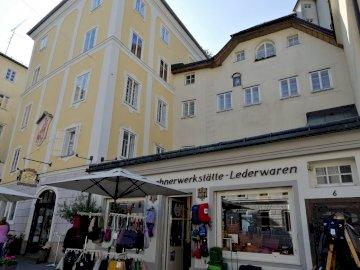 w Salzburgu - budynki i sklepy w Salzburgu. Grupa ludzi przed budynkiem.