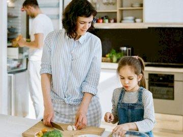 Sto aiutando la mamma - L'immagine mostra un bambino che aiuta sua madre in cucina. Un ragazzo seduto a un tavolo a