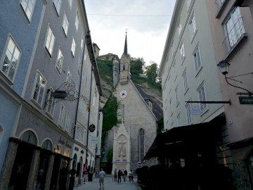 w Salzburgu - widok na uliczkę i kamienice - Salzburg. Zegar z boku budynku.
