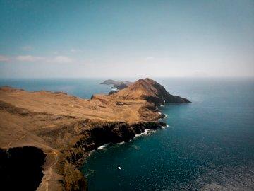 Împușcat drone la Ponta de São - Muntele maron alături de marea albastră sub cerul albastru în timpul zilei. Un corp de apă cu un