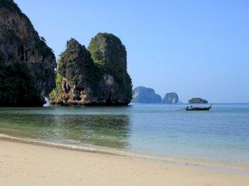 Seascape z łodzią na - Brown i zielona rockowa formacja na morzu podczas dnia. Wyspa pośrodku akwenu z plażą Railay w tl