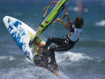 Surfing experience - surf, sun, sea, water, wind, sun. A man flying through the air while riding a wave in the ocean.