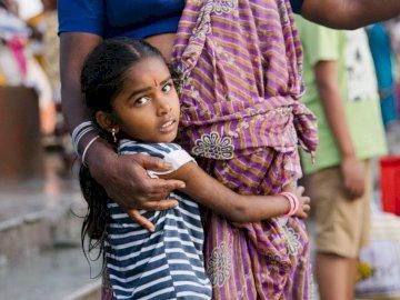 Junges indisches Mädchen und sie - Mädchen, das graues und weißes Hemd trägt.