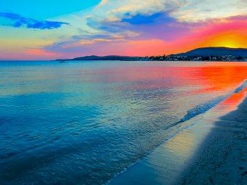 Wieczorna plaża - piękna plaża wieczorem, z domami w tle. W kolorach czerwonym i niebieskim. Zachód słońca nad ak