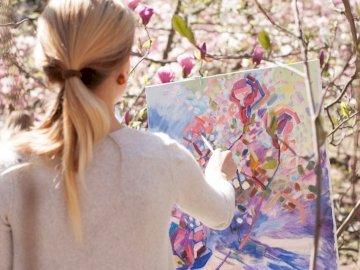 Maler im Botanischen - Frau im weißen Langarmhemd, das weiße und blaue Blumenmalerei hält. Eine Frau, die in einem Park