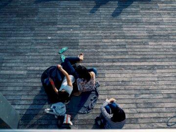 Casal relaxando em um cobertor - Pessoa deitada no piso de madeira. Um homem sentado em um banco em frente a um prédio.