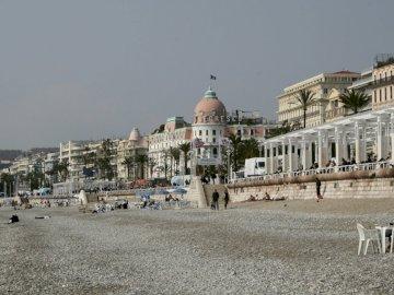 Azurblaue Küste - Urlaub an der französischen Riviera. Eine Gruppe von Menschen, die vor einem Gebäude gehen.