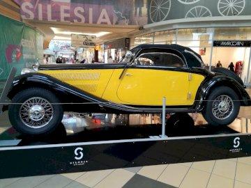 mercedes old timer - Mercedes retrô no shopping. Um carro preto e amarelo estacionou ao lado de um edifício.