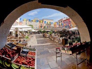 Riviera Francesa - restaurantes, puesto de frutas ---------. Una persona sentada en una mesa frente a un edificio.