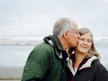 Estos son mis padres. Esta - Hombre besando a mujer en cheque al lado del cuerpo de agua. Un hombre y una mujer de pie junto a un