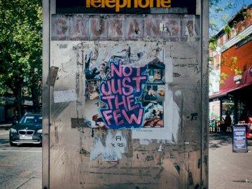 Não apenas os poucos, grafite em - Foto de close-up da cabine telefônica. Manchester, Inglaterra. Um edifício com pichações ao lado