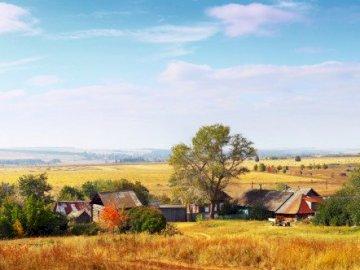 Un pueblo tranquilo - La imagen muestra un pueblo tranquilo y apacible. Un gran campo verde con árboles en el fondo.