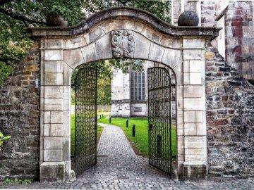 Porte de pierre - entrée dans un monde extraordinaire. Un bâtiment en pierre avec un banc devant un mur de briques.