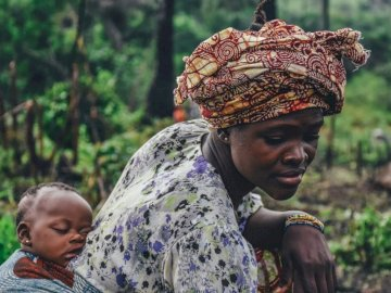 Mother and baby cassava - Woman carrying baby on back. New Forest National Park, UK. A man wearing a hat talking on a cell pho