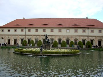 Czech Prague - Gardens and fountain in the park on the Vltava River. A small house surrounded by water.