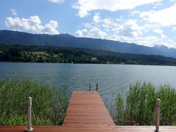 bridge on the lake - jetty on the lake, resort, nature. A wooden bench sitting next to a body of water.