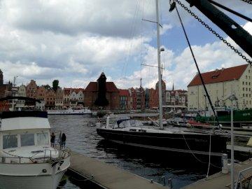 w Gdańsku - widok  na stary dźwig portowy, żuraw. Łódź jest zadokowana obok akwenu.