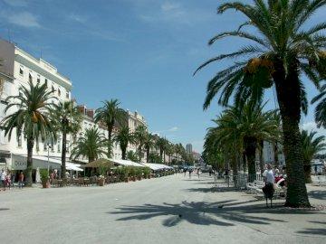Ville croate - Trogir, ville croate. Un homme monté sur une planche à roulettes dans une rue à côté d'un
