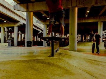Шлайфане в скейтпарка - Мъж в червена тениска и черни панталони прави упражнен