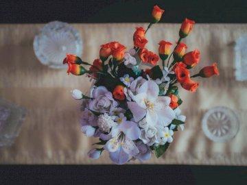 Weiße und rote Kunstblumen - Orange und weiße Blumen auf dem Tisch. Rumänien, Cluj-Napoca. Eine Blumenvase auf einem Tisch.