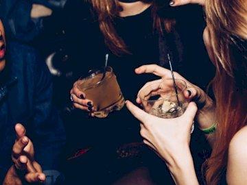 Gros plan de boissons au club - Deux femmes parlent tout en tenant des verres. Austin, TX