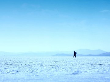 Fisherman returns from fishing - Person walking on ice field photo. Russia.