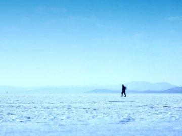 Fischer kehrt vom Fischen zurück - Person, die auf Eisfeldfoto geht. Russland.