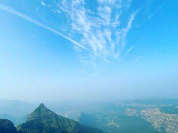 Belleza escénica - Montañas verdes bajo el cielo azul durante el día. Una vista de una gran montaña en el fondo.