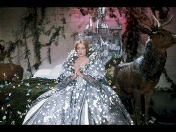 Catherine Deneuve - Rochie de culoare soarelui. Catherine Deneuve stând în fața unei statui.