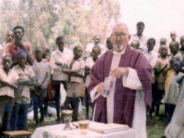 Padre Cieślak - Puzzle di Father Cieślak. Un gruppo di persone in piedi intorno a un tavolo.