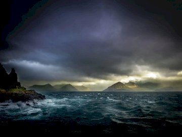 Seasick, nature - Landscape photo of waters, mountains, and black clouds.