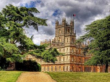 Highclere Hampshire - Inglaterra Highclere Hampshire. Wieża zegarowa przed drzewem z zamkiem Highclere w tle.