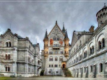 Schwangau Neuschwanstein - Alemania Schwangau Neuschwanstein. Un castillo con un reloj en la parte delantera de un edificio.