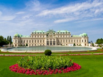 Vienna Schonbrunn Palace - blooming garden ------------------. A large building with a clock on top of a lush green field with