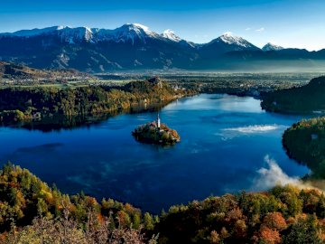 Island of Bled - Slovenia - islet with a church. A body of water with a mountain in the background.